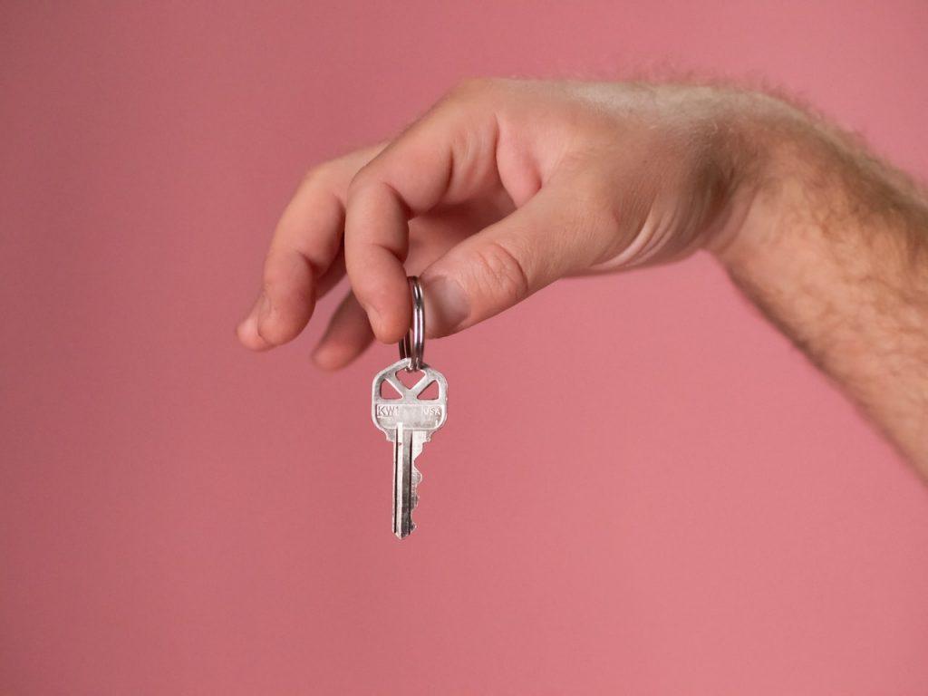Fond rose, main tenant une clé